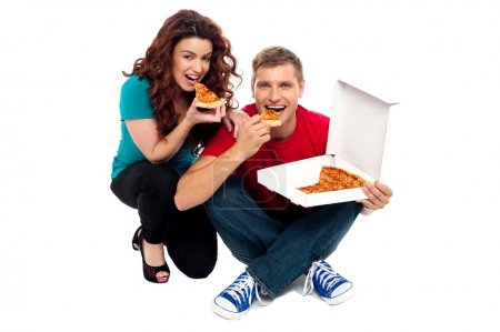 Photo for Young couple sitting on floor and enjoying yummy pizza - Royalty Free Image