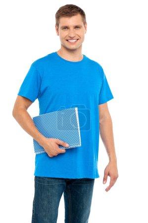 Smiling guy holding spiral notebook