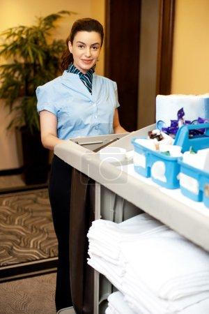 Photo pour Charmant exécutif féminin tenant chariot d'articles de toilette et posant devant la caméra - image libre de droit