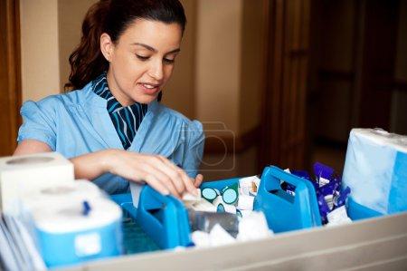 Photo pour Jolie femme de ménage occupée à travailler. Vérification et organisation de tous les articles de toilette dans le panier - image libre de droit