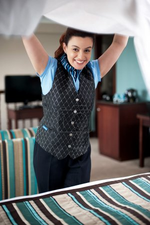 Photo for Charming female housekeeper replacing the sheets. Led tv in the background - Royalty Free Image