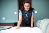 Smiling female executive giving final touches to master bedroom