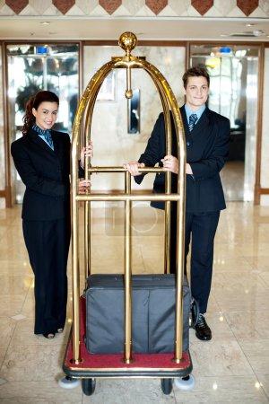 Photo pour Concierge collègues tenant un chariot à bagages avec des bagages sur elle - image libre de droit