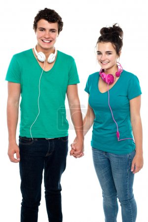 Photo for Charming happy young couple with headphones around their necks, holding hands. Great bonding - Royalty Free Image