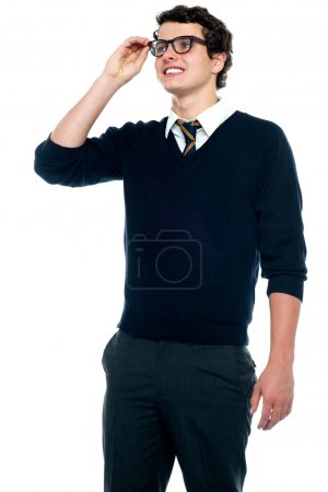 Innocent schoolboy adjusting his eyeglasses