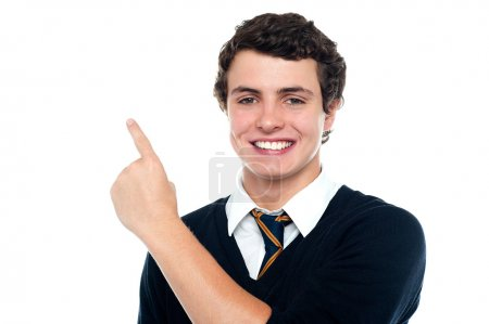 Photo pour Beau jeune homme en uniforme qui indique vers le haut. le tout sur fond blanc - image libre de droit