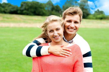 Photo pour Le mari serre sa femme dans ses bras. Main juste au-dessus de sa poitrine. Plan extérieur - image libre de droit