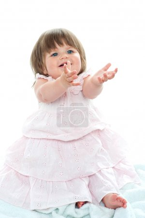 Adorable blonde baby asking for her toys