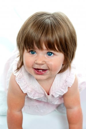 Baby girl with milk teeth crawling on the ground
