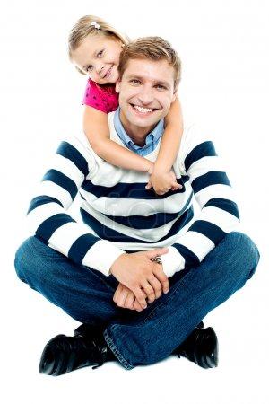 Photo pour Père en hiver, assis par terre, les jambes croisées, sa fille le tenant par derrière - image libre de droit