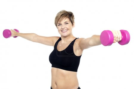 Fitness woman working out with pink dumbbells