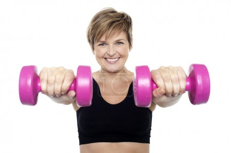 Lady holding pink dumbbells. Arms outstretched