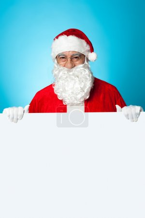 Photo for Aged Santa standing behind a blank ad board, marketing concept. - Royalty Free Image