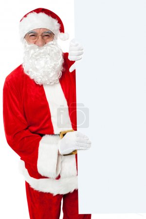 Aged Santa holding blank white banner ad board