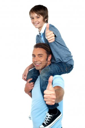 Confident father carrying his son on shoulder