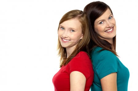 Photo for Joyous mom and daughter standing back to back and turning their faces towards camera. - Royalty Free Image