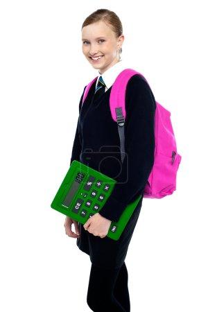 Photo pour Pose latérale d'une jolie écolière posant avec sac à dos et calculatrice . - image libre de droit