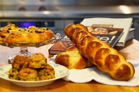 Photo pour Assortiment d'eau à la bouche de boulangerie soigneusement disposées ainsi que des livres de recettes. - image libre de droit