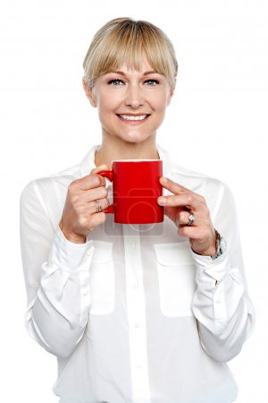 Female manager posing with coffee mug in hand