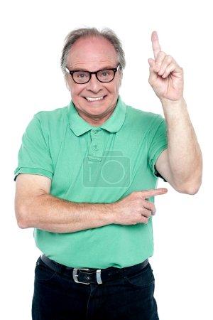 Happy old man pointing upwards
