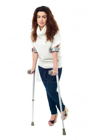 Sad faced woman limping with crutches