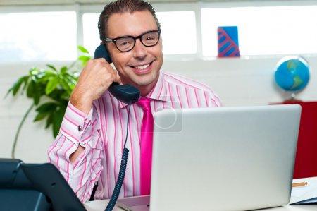 Photo pour Représentant masculin souriant engagé sur un appel d'affaires avec ordinateur portable devant lui . - image libre de droit