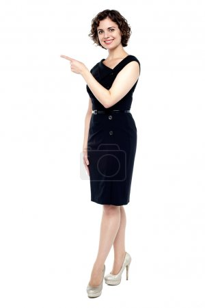 Charming woman pointing towards copy space area
