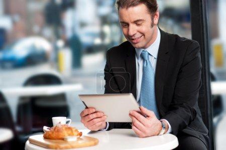 Photo pour Chef d'entreprise mâle examinant les affaires mises à jour sur tablet pc en attendant sa commande. - image libre de droit