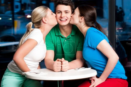 Two girls kissing handsome young boy