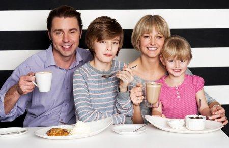 Photo pour Heureuse famille de quatre personnes appréciant leur petit-déjeuner dans un restaurant. - image libre de droit