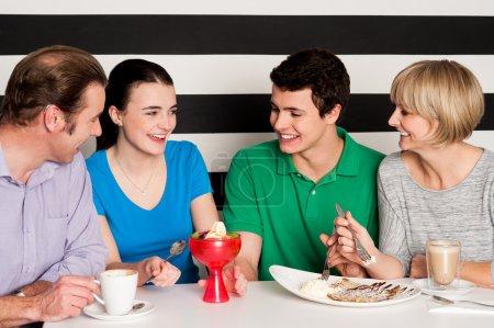 Photo pour Joyeuse famille de quatre savourant eatables délicieux et dessert. - image libre de droit