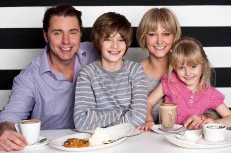 Photo pour Joyeuse famille caucasien de quatre s'amuser au restaurant. - image libre de droit