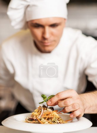 Photo for Handsome male chef dressed in white uniform decorating pasta salad. - Royalty Free Image