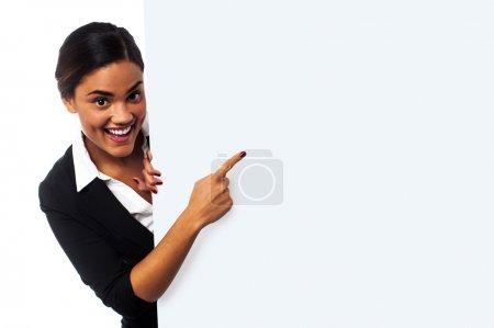 Photo pour Charmante femme pointant au Conseil ad blanc vierge, concept d'entreprise - image libre de droit