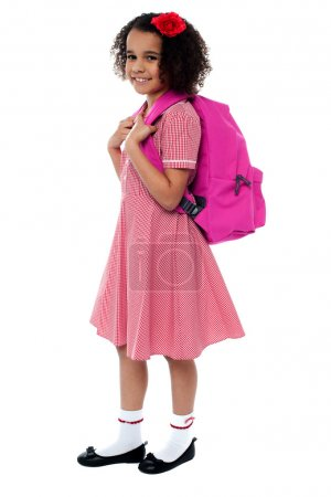Photo for Curly haired school girl in uniform carrying pink backpack on shoulders. - Royalty Free Image