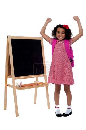 Excited beautiful little girl in school uniform