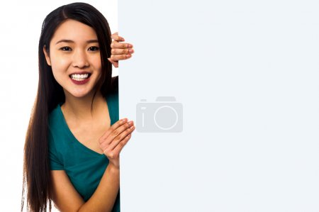 Photo for Smiling female model popping from behind big blank whiteboard. - Royalty Free Image