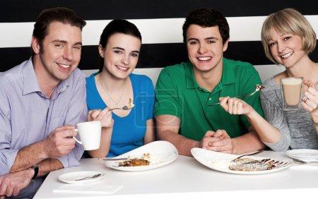 Photo pour Joyeuse famille de quatre personnes savourer le petit déjeuner une cuisine agréable et shake chocolat. - image libre de droit