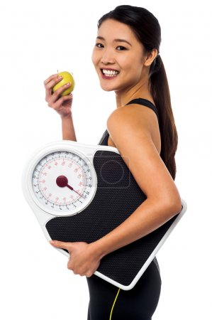 Photo for Fitness instructor holding fresh green apple and weight scale. - Royalty Free Image