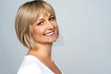 Photo for Pretty middle aged lady posing over grey background - Royalty Free Image