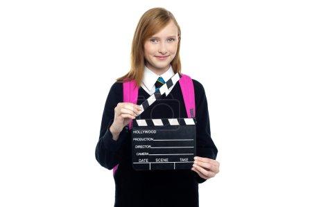 Photo pour Mignon écolière avec un clapperboard - image libre de droit