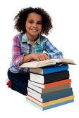 Happy schoolgirl reading a textbook
