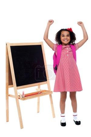 Jubilant little girl in school uniform