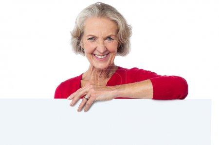 Photo pour Femme âgée souriante dans les occasionnels derrière le panneau d'affichage - image libre de droit