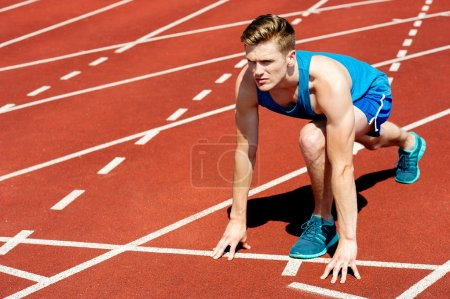 Photo for Young muscular athlete is at the start of the race - Royalty Free Image