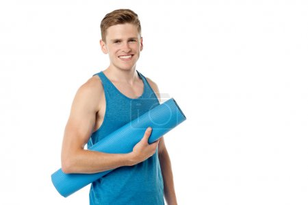 Male gym instructor holding blue mat