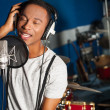Young male singer in recording studio...