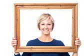 Middle aged lady holding photo frame