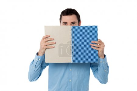 Young man hiding his face with notebook