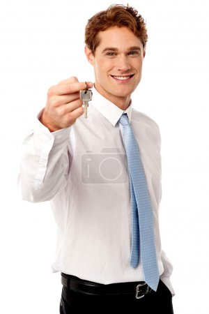Smiling man offering house key